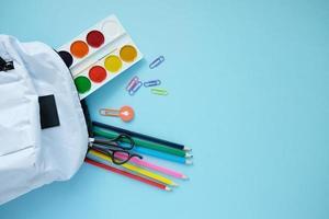 mochila con diferentes colores de papelería en la mesa. foto