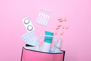 Cold season, a pack of medicines on a pink background. photo