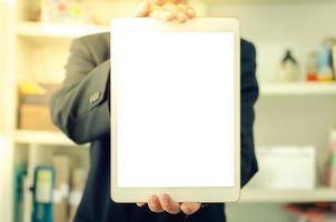 empresario sosteniendo una tableta de pantalla táctil blanca en blanco. se utiliza para poner texto o información para anunciar noticias o vender productos en línea. concepto de negocio de marketing foto