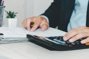 Business Man using calculator at a desk. Business finance, tax, and investment concepts. photo