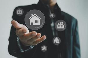 compra, venta y alquiler de casas o concepto de bienes raíces, propiedad en línea, manos del empresario en un concepto de pantalla virtual. foto