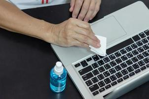 Spraying alcohol to clean the computer and wipe the germs. Health care concept. photo