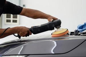 detalle del coche - mecánico masculino que sostiene la máquina pulidora del coche. industria automotriz, taller de pulido y pintura y reparación de automóviles. foto