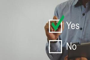 businessman holding a pen with a green check mark on the square on a virtual screen photo