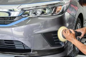 Car detailing - Male mechanic holding car polishing machine. Auto industry, car polishing and painting and repair shop. photo