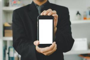 empresario sosteniendo un teléfono inteligente con pantalla táctil en blanco. se utiliza para poner texto o información para anunciar noticias o vender productos en línea. concepto de negocio de marketing foto