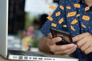 hombre de primer plano sosteniendo un teléfono celular un icono de mensaje de correo electrónico. Comercialización de empresas que envían información a los clientes o pirateo de transacciones en línea. tecnología de concepto de negocio. foto