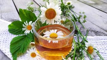 Chamomile tea. Drink with chamomile flowers. Flowers and a cup with tea on a wooden background. photo