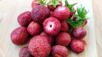 Close-up strawberries with leaves. Ripe red berries lie in a heap on the table. Delicious aromatic berries, top view. photo