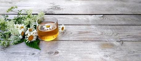 Chamomile tea and a bouquet of chamomiles. Glass cup with tea on wooden boards. photo