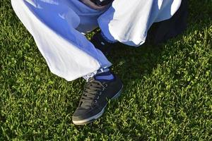 Legs of a teenage girl in blue jeans. The girl is sitting on the grass on the football field. photo