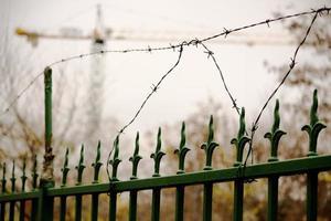 Verja de hierro forjado verde con alambre de púas foto