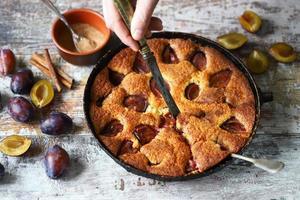 Slice of plum pie on a fork Homemade American plum pie. photo