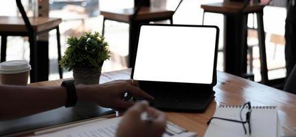 empresaria usando la pantalla en blanco de la computadora portátil mientras trabaja con la calculadora financiera. trazado de recorte foto