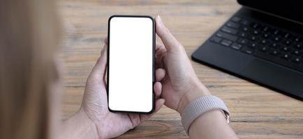 Cerrar la mano de la mujer usando un teléfono inteligente con pantalla en blanco en la cafetería cafetería. foto