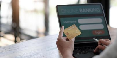 Online payment,woman's hands holding a credit card and using laptop computer for online shopping with vintage filter tone photo