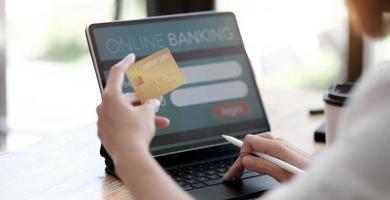Pago en línea, manos de mujer sosteniendo una tarjeta de crédito y usando una computadora portátil para compras en línea con tono de filtro vintage foto