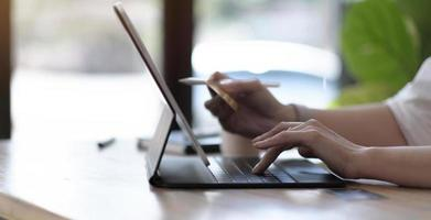 Mujer usando laptop con calculadora y tarjeta de crédito en la mesa, compras en línea foto