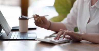Contador de mujer que trabaja en la oficina con calculadora y sosteniendo la tarjeta de crédito, primer plano de las manos, banner panorámico. concepto de compra online. foto
