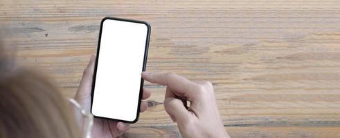 Imagen de maqueta en blanco teléfono celular con pantalla blanca. Mano de mujer sosteniendo mensajes de texto usando el móvil en el escritorio en la oficina en casa. foto