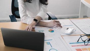 Cerrar joven mujer de negocios revisando las estadísticas económicas del proyecto, calculando las ventas o inversiones financieras, analizando gráficos económicos y cuadros en la computadora, administrando el presupuesto. foto
