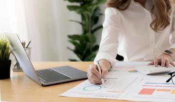 mano de empresaria sosteniendo la pluma y apuntando al papeleo financiero con el diagrama de la red financiera. foto