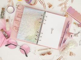llave plateada en la página blanca del planificador. diario abierto con página blanca y holográfica. vista superior del planificador rosa con papelería. foto de decoración de planificador de glamour rosa