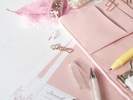 Papelería planificador de oro rosa. amor de letras en forma de alfiler. Lápiz blanco y planificador rosa sobre fondo blanco. foto