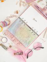 llave plateada en la página blanca del planificador. diario abierto con página blanca y holográfica. planificador rosa con lindos artículos de papelería. vista superior del planificador rosa con papelería. foto