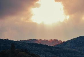 un agujero en el cielo: el sol ilumina la cima de la montaña foto