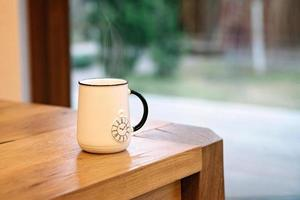 A soaring white cup with a picture of a pocket watch on a wooden table. photo