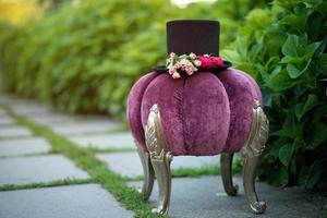 Alice in Wonderland. Hat cylinder decorated with flowers roses on a decorative purple pouf. Soft selective focus. photo