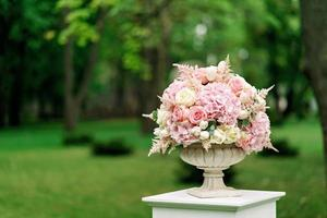 A beautiful bouquet of flowers in a stone vase stands on a column on a green background. Decor for the wedding ceremony. Copy space. photo