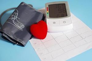 tonómetro y corazón de juguete rojo en el fondo de un cardiograma. concepto de salud. cardiología: cuidado del corazón. foto