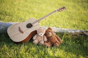 dos osos de peluche enamorados en la hierba con una guitarra en un día soleado de verano. día de San Valentín. concepto de amor y fidelidad. parejas gay foto