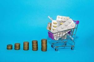 una pila de monedas en una fila con un carrito de la compra con medicamentos sobre un fondo azul. salto del concepto del salto del precio de los medicamentos. pandemia de coronovirus covid-19 foto