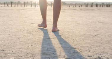 Close up of male barefoot legs walk in the hot summer desert, global warming concept video
