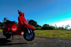 Vintage scooter stands and blue sky photo
