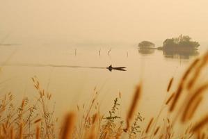 Beautiful view shadows Light Long-tailed boat sunrise in dam Srinakarin National park Kanchanaburi, Thailand photo