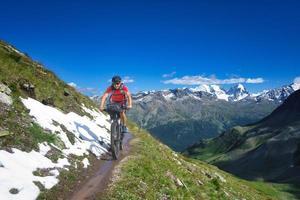 Ciclista en sendero de montaña en un hermoso paisaje de los Alpes foto