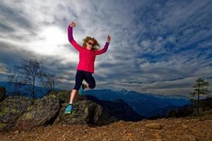 niña salta de rocas en las montañas durante un entrenamiento foto