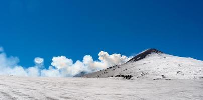 Cráter de la cumbre del volcán Etna con anillo de humo espectacular fenómeno de vapor areola durante la erupción foto