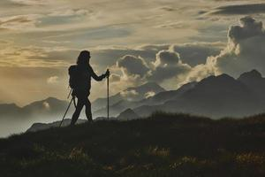 Walk in solitude on the Alps. A woman on with the background of abstract mountains in the clouds photo