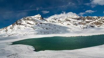 Deshielo en un paisaje de alta montaña con un lago. foto