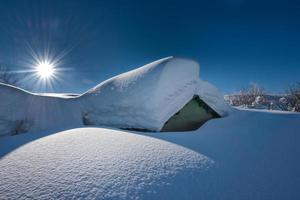 Small house covered with a lot of snow after heavy snowfall photo