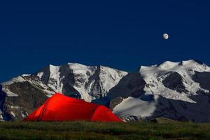 Tent in the solitude beneath the glaciers of the Alps photo