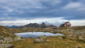 Alpine hut near small mountain lake photo