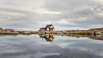 Small alpine hut mirrored in mountain lake photo