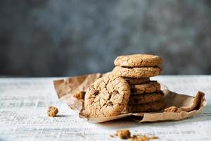 Stack of fresh oatmeal cookies with chocolate lies on a table photo