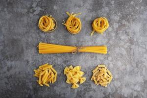 Five types of different pasta lie on a gray table photo